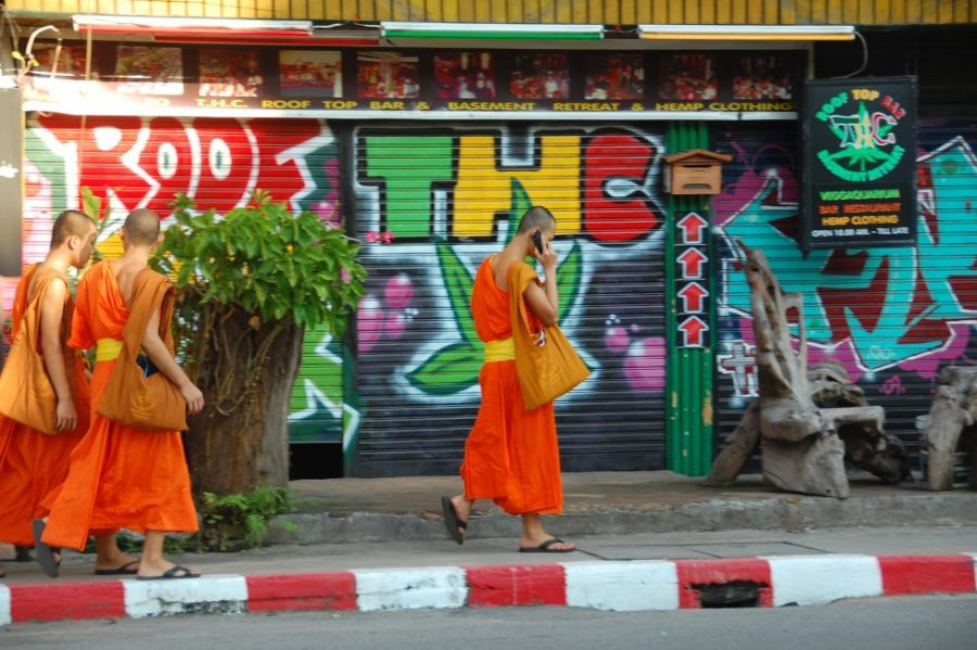 Monk in Thailand walks with a smartphone